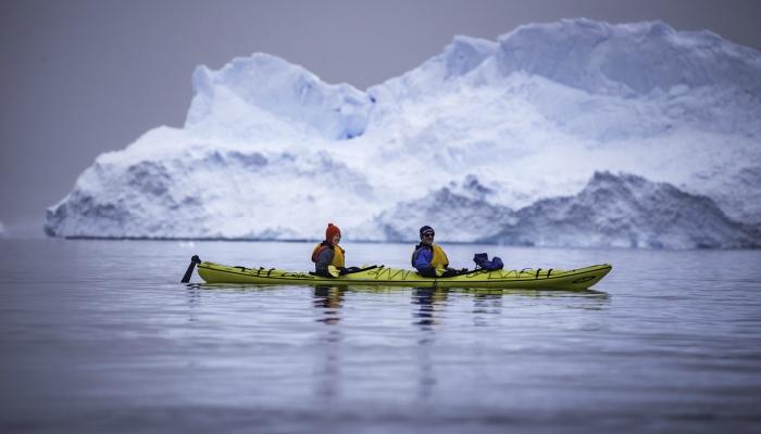 Sea kayaking past icebergs in Antarctica.
