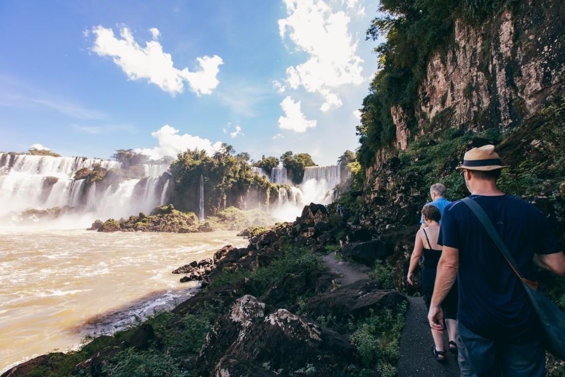Travellers walk around Iguazu Falls