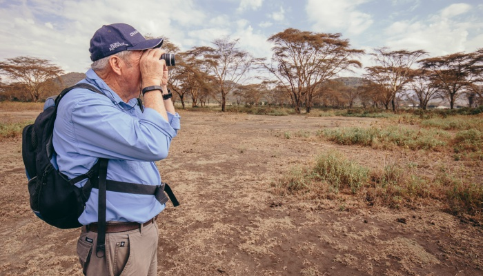 Traveller with binoculars on safari in Tanzania
