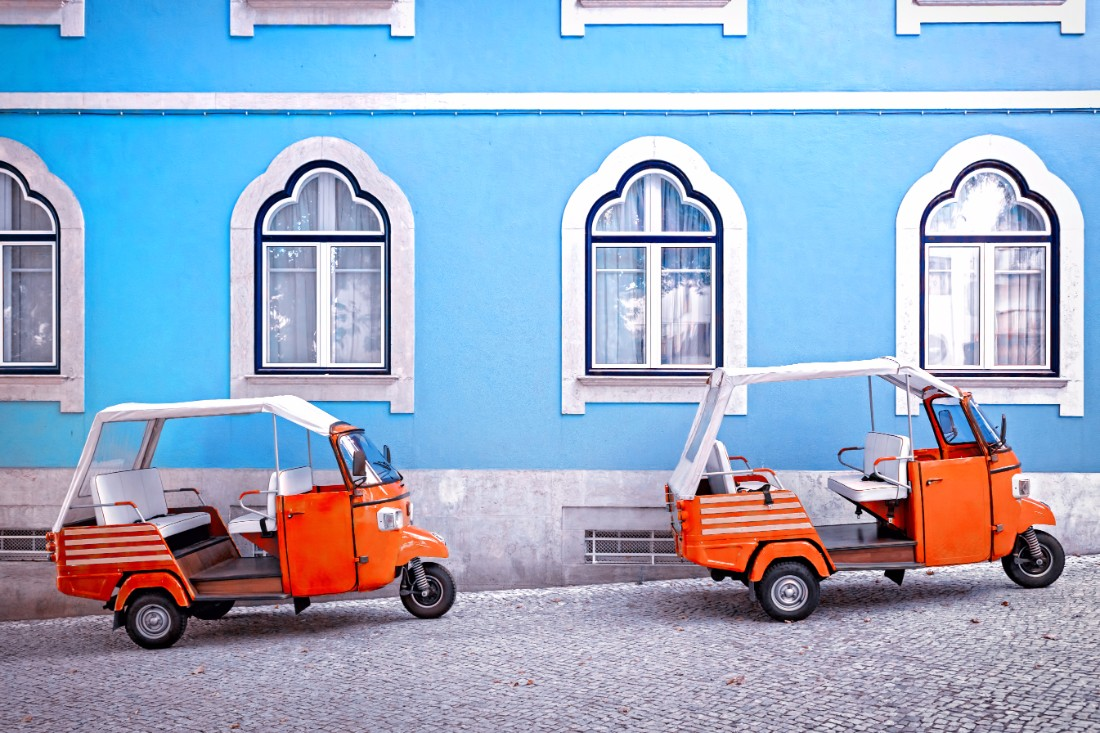 Two orange tuktuks parked in front of a blue house in Lisbon