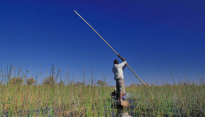 Man steers a mokoro on the Okavango Delta