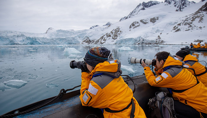 Travellers taking photos of a glacier in Svalbard, Norway.