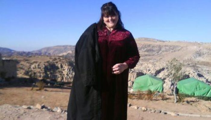 Carla Dressed like a local - a glass of sweet Bedouin tea in hand.