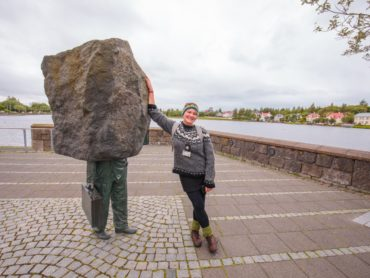Woman poses next to statue in Reykjavik