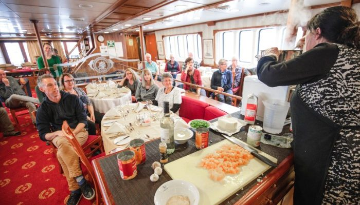 Passengers on a boat watch a cooking demonstration