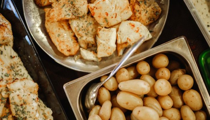 Fish and potatoes in trays.
