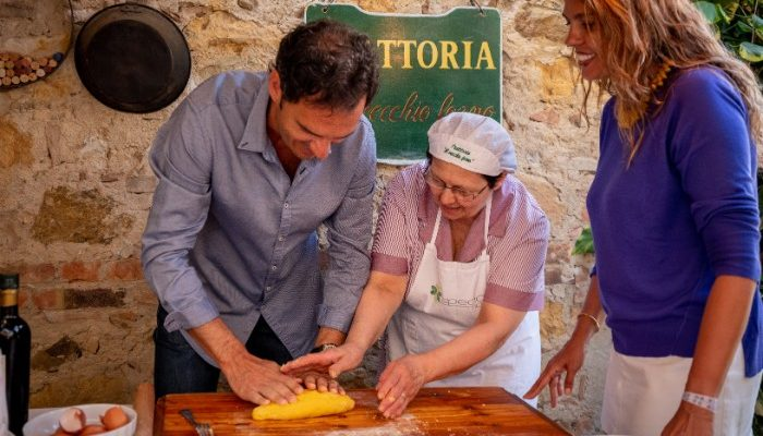 a couple learning to make pasta in Italy