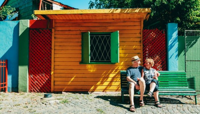 Happy couple sitting in front of colourful houses