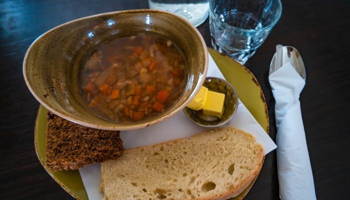 A bowl of stew with bread and butter