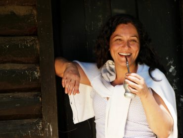 Smiling woman holding a cup of mate