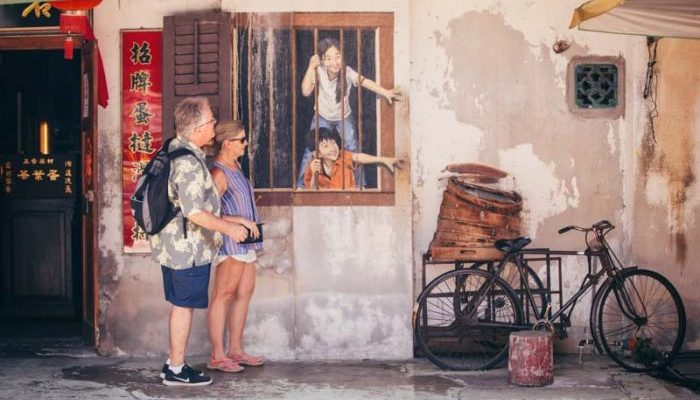Two travellers looking at street art in Malaysia