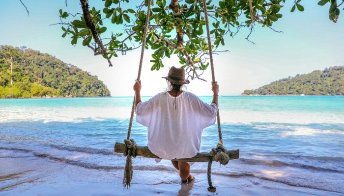 Traveller sits on a swing overlooking the water