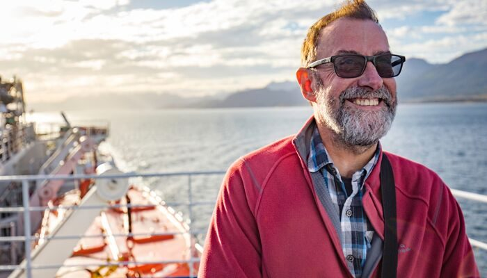 A smiling older man on the deck of a boat
