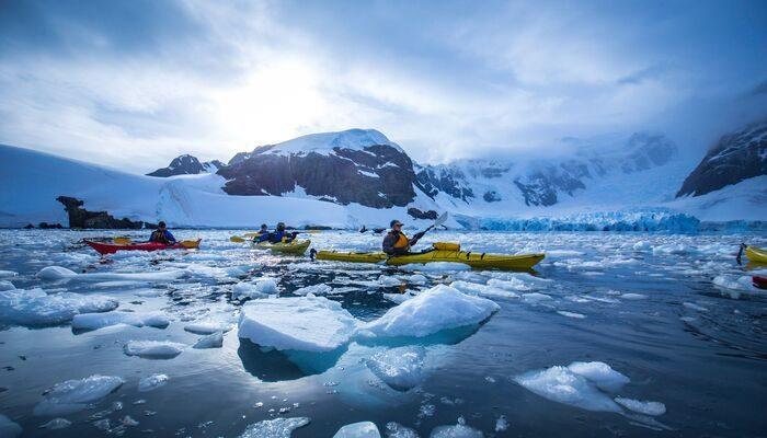 Travellers kayaking in Antarctica