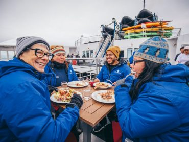 group in antarctica on ship eating
