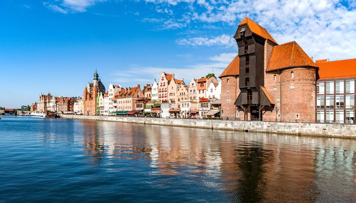 Gdansk waterfront image with old orange roof buildings and blue water.