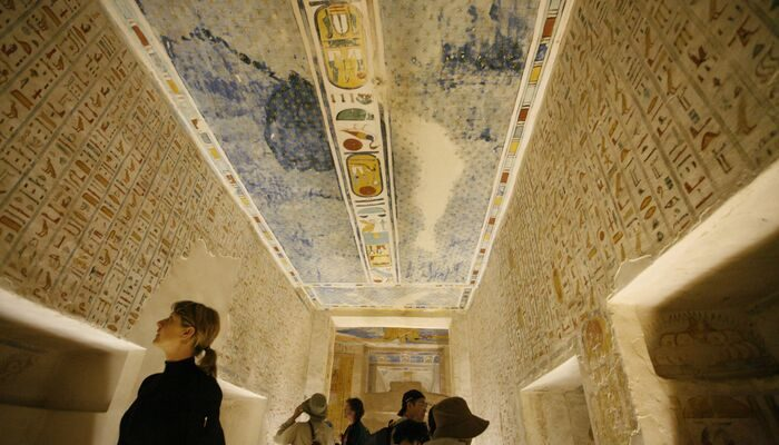 People inside a tomb in Egypt looking at the details roof.
