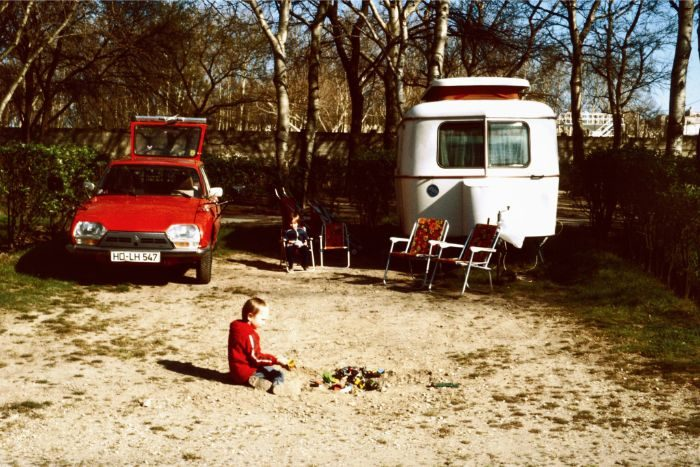 Old photoo of a child and two cars in the background