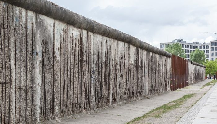 Photo of the berlin wall with dark concrete and a building in the distance