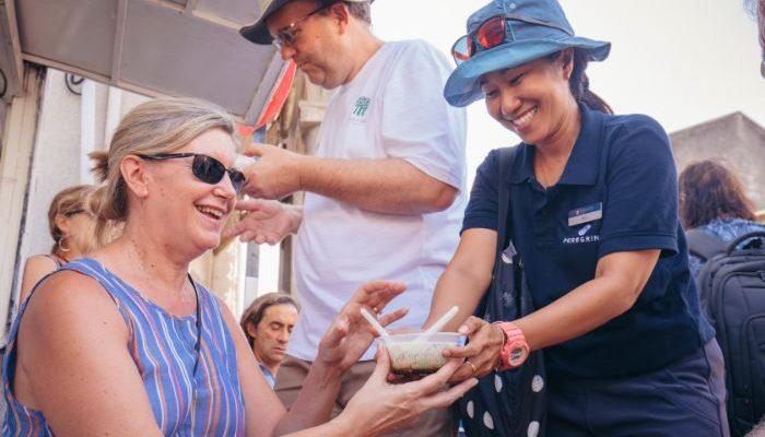 A tour leader hands a traveller a bowl of dessert