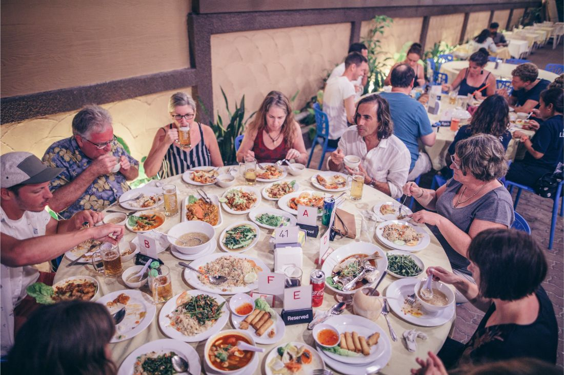 A group of travellers sit around a table covered in plates of food