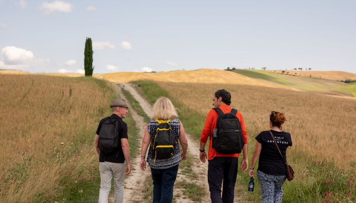 Four people walking along the trail in Tuscany looking away into the horizon away from the camera