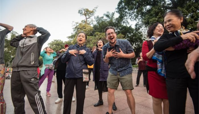 A group of people laughing at a yoga class in Hanoi