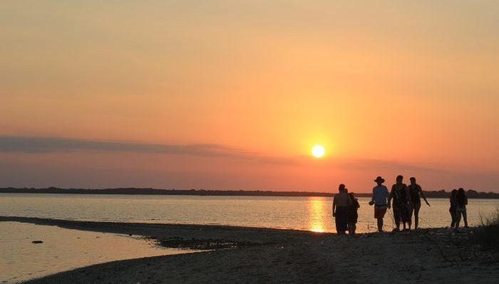 Travellers on the beach watch a sunset