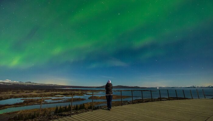 A person watches the Northern Lights in Iceland