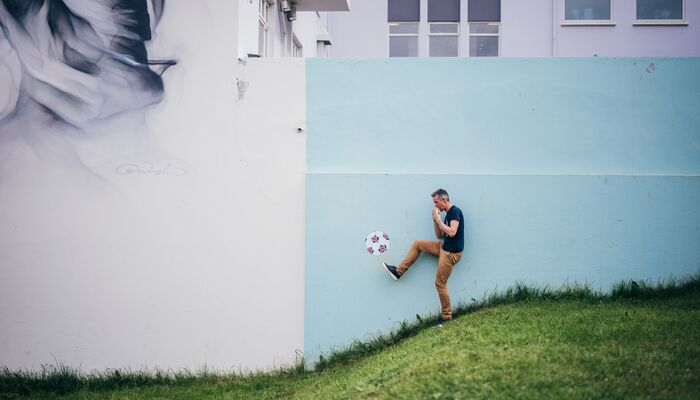 A man pretending to kick a soccer ball while eating a hotdog in Iceland