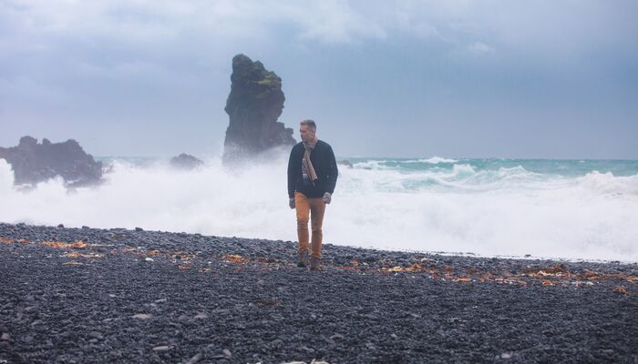 A man walking along a black sand beach with ferocious waves in the background