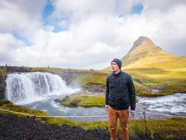 A man rugged up in a jacket and hat in front of a waterfall in Iceland.