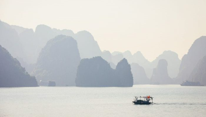 A fishing boat in Halong Bay at sunrise