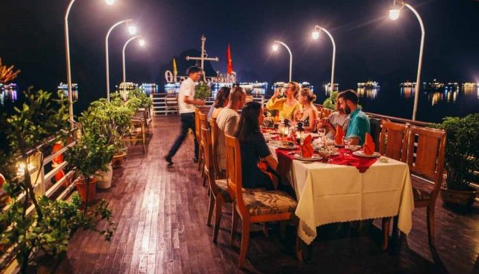 Travellers having dinner on the top deck of a boat on Halong Bay