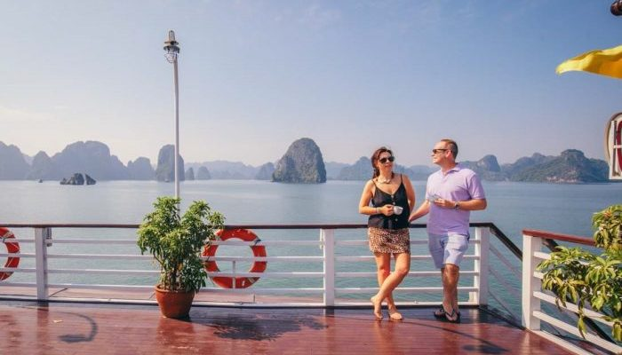 Two people standing on the deck of a boat on Halong Bay