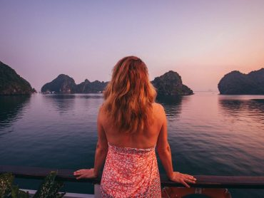 A woman looks out over Halong Bay at dusk