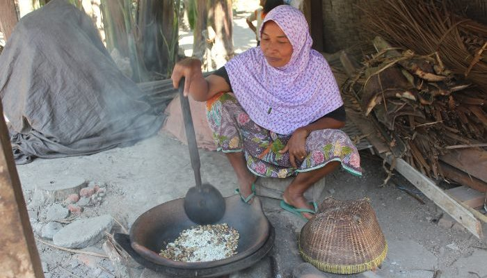 A woman roasts coffee beans over the fire.