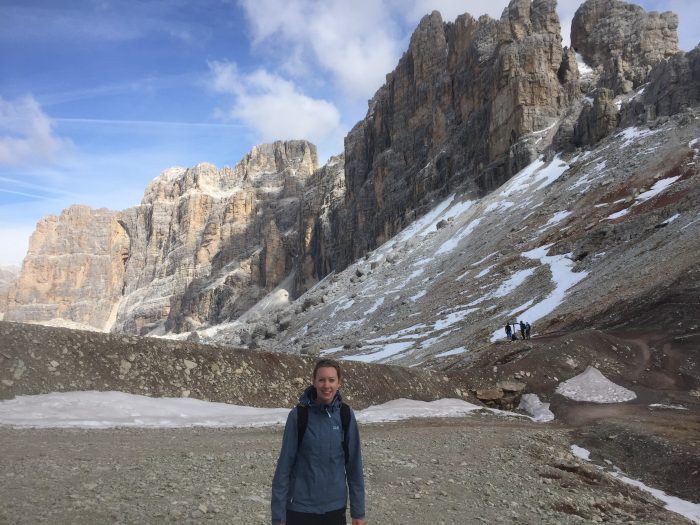 Photo of a person standing in front of the Dolomites