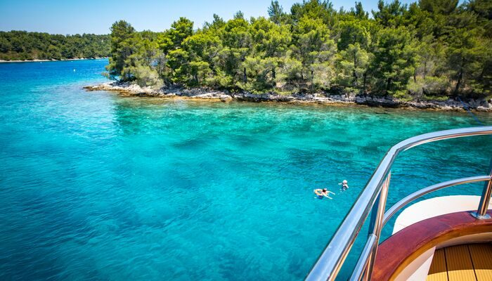 People swimming off the boat in Croatia in verey clear, blue water with some trees in the background
