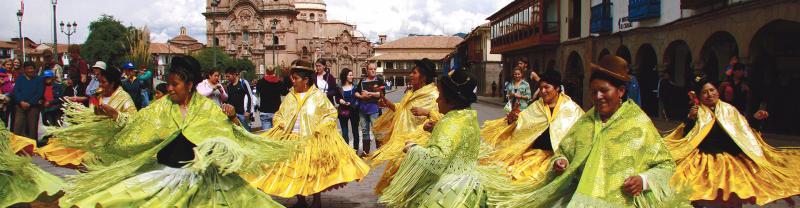 Locals in traditional dress dancing in the street, Cusco, Peru