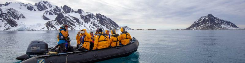 Passengers on board zodiac with snow capped mountains behind