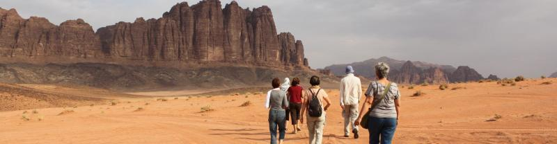 A group of travellers walking in the desert