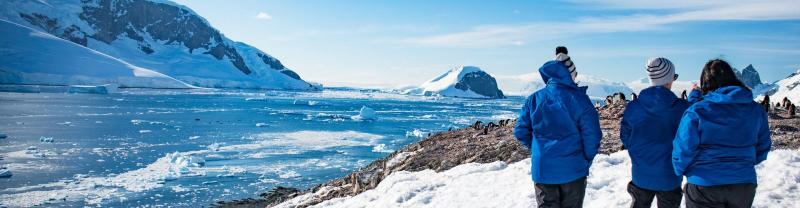 Travellers standing on Antarctica